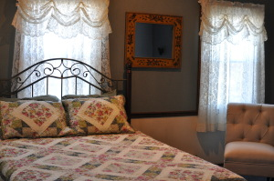 photo of bed, chair and two windows with lace curtains